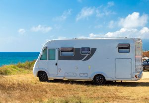 A caravan & Motorhome parked on a cliff near the sea.