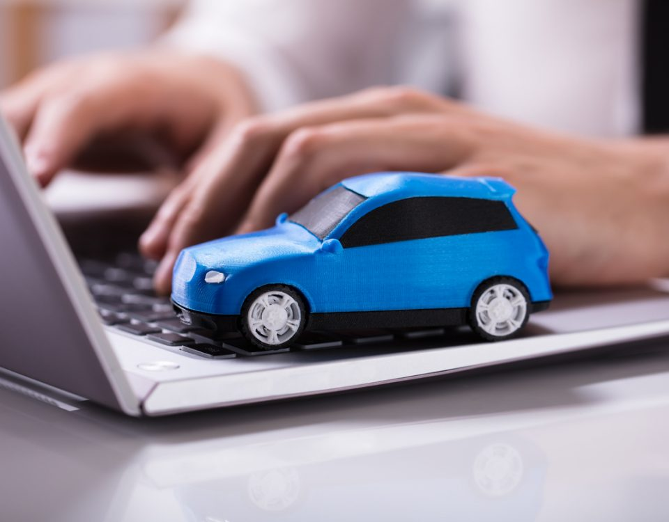 Close-up Of A Small Blue Car On Laptop Keypad